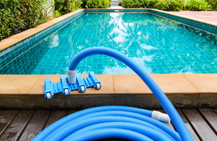 Pool vacuum cleaning flexible hose on the pool